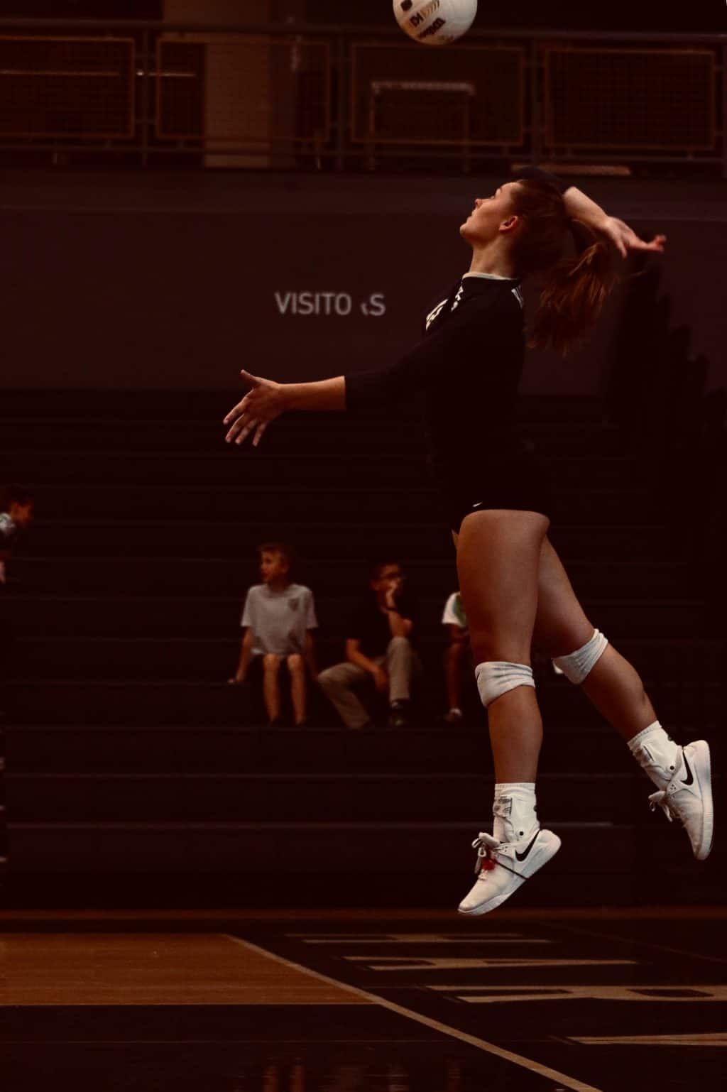 Female volleyball player spiking a ball