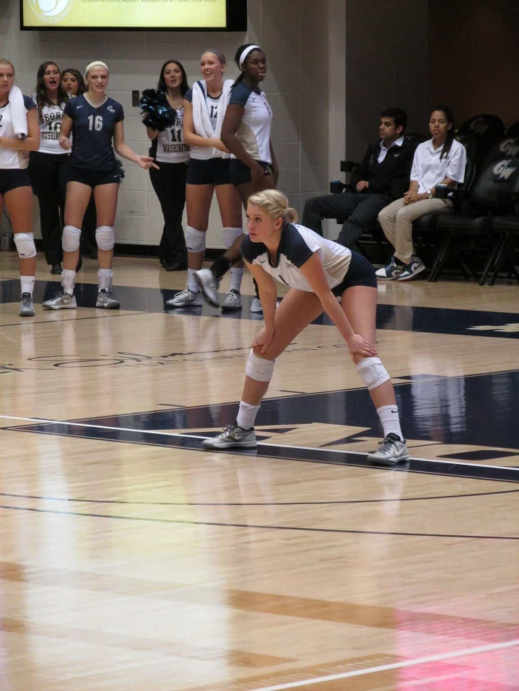 Volleyball player with hands on her knees
