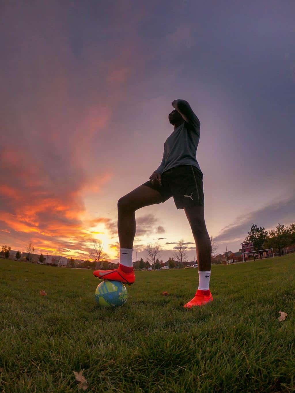 Man on grass field stepping on a soccer ball