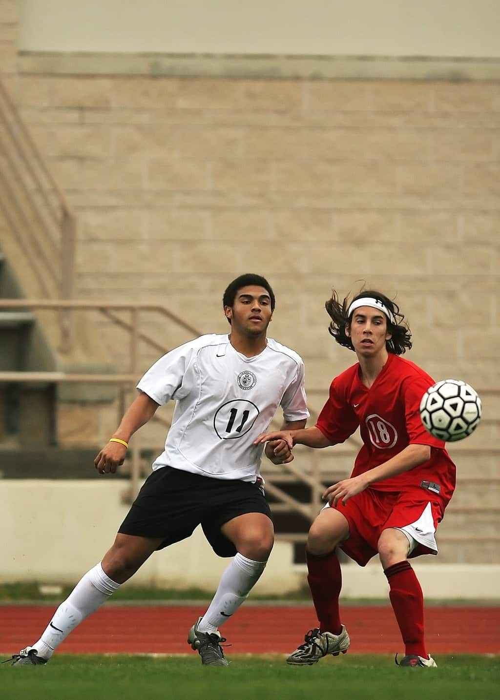 Two soccer athletes vying for the ball