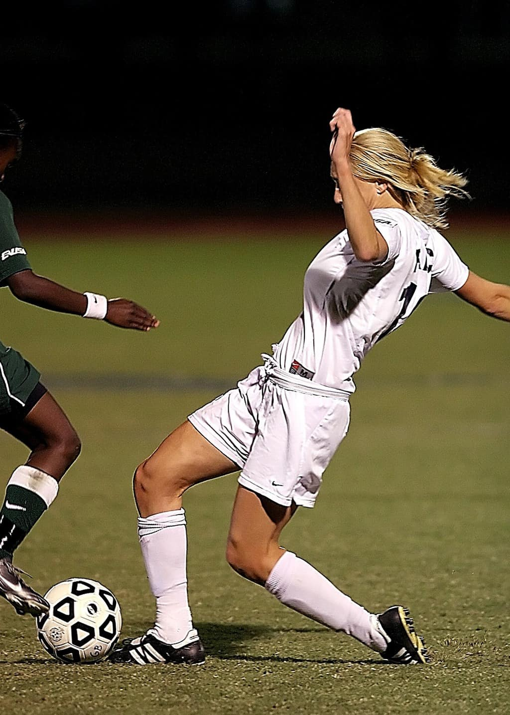 Woman in white soccer jersey kicking a ball