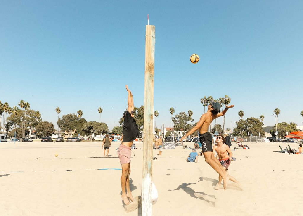 People playing beach volleyball with player about to spike