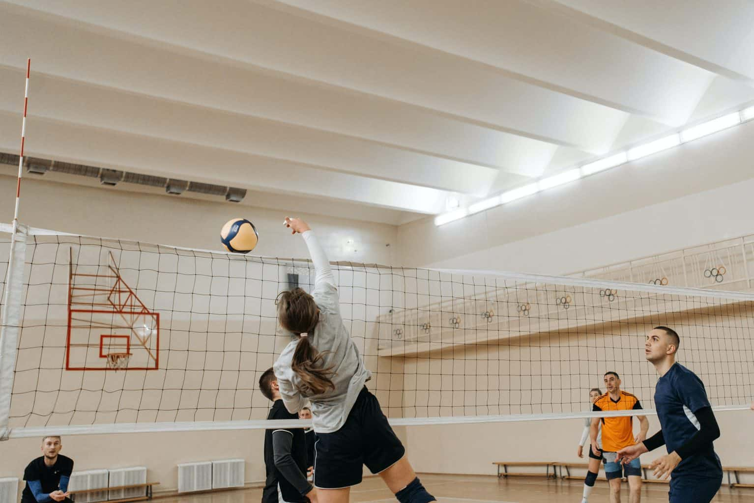 A volleyball player spiking th ball over the net