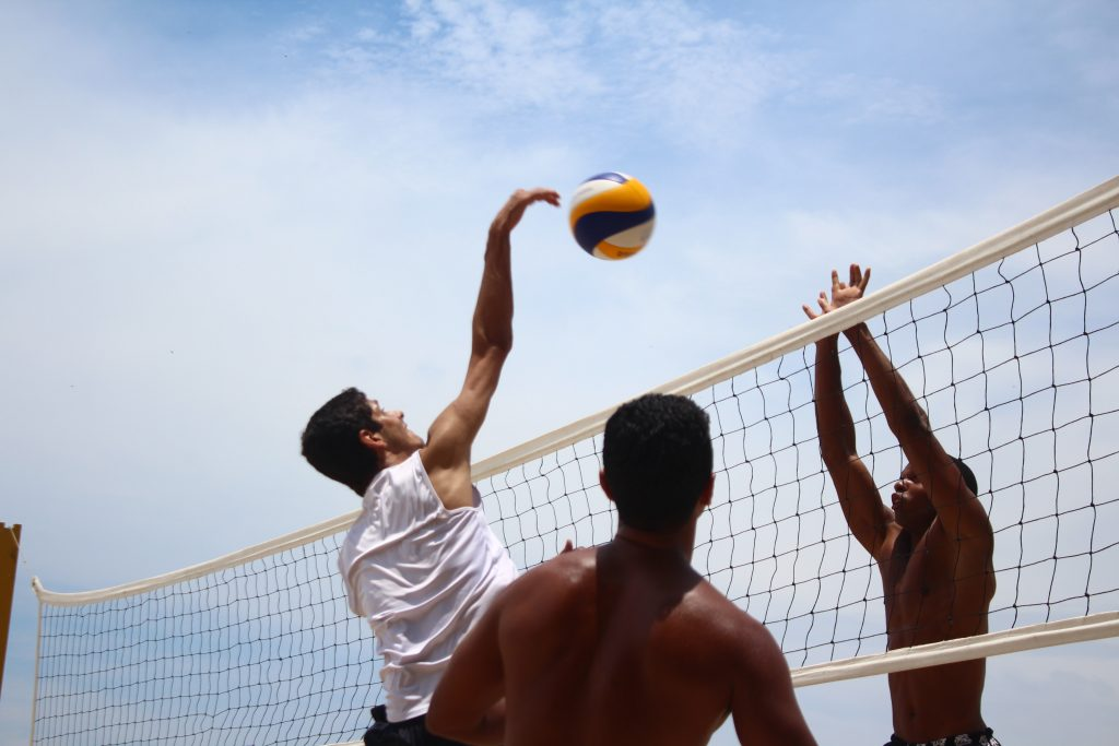Volleball player with arm over the net