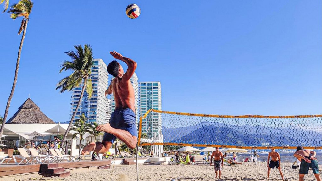 A volleyball player doing a jump serve with high vertical