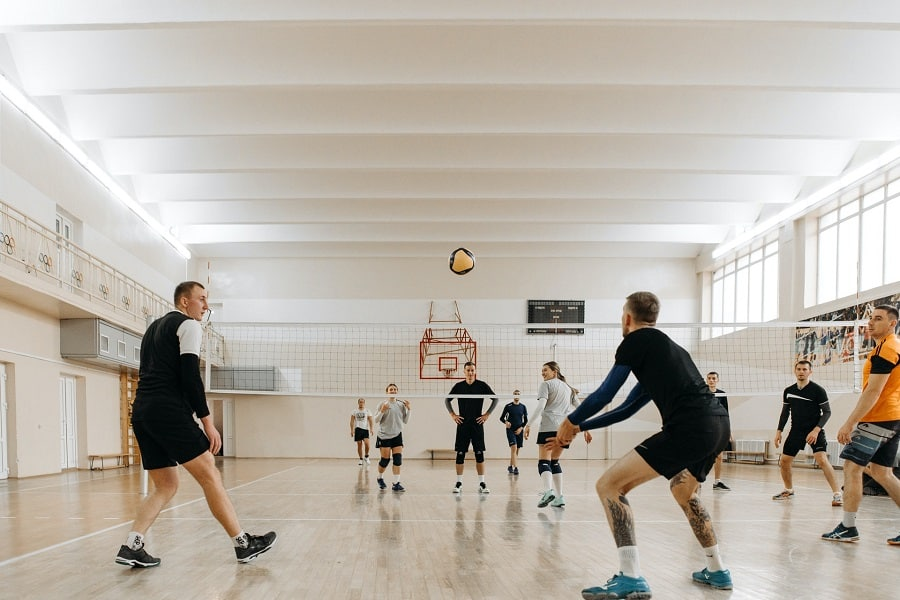 Two teams playing volleyball in an indoor court