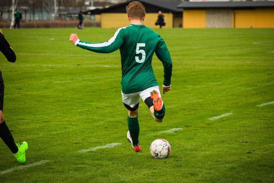 Player in green jersey kicking a ball