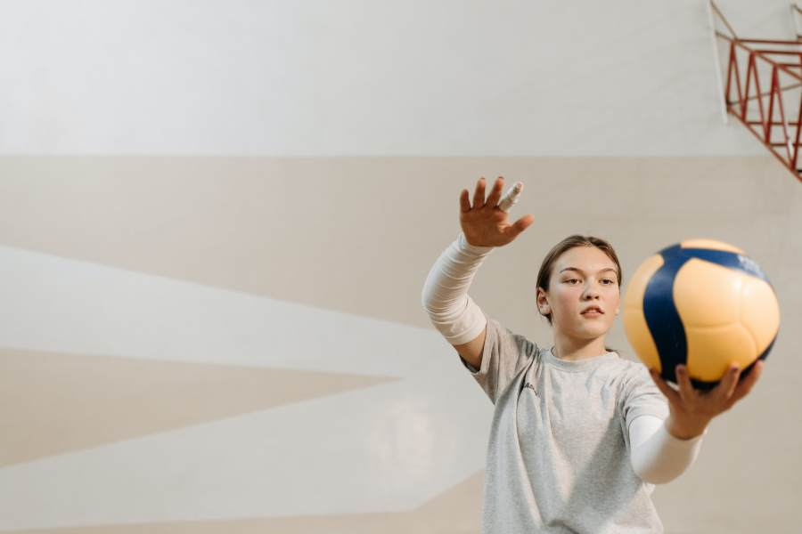 Volleyball player raising her right hand to serve the ball
