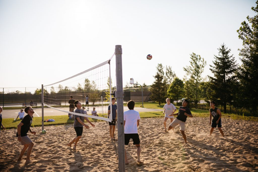 People playing volleyball on a sand floor