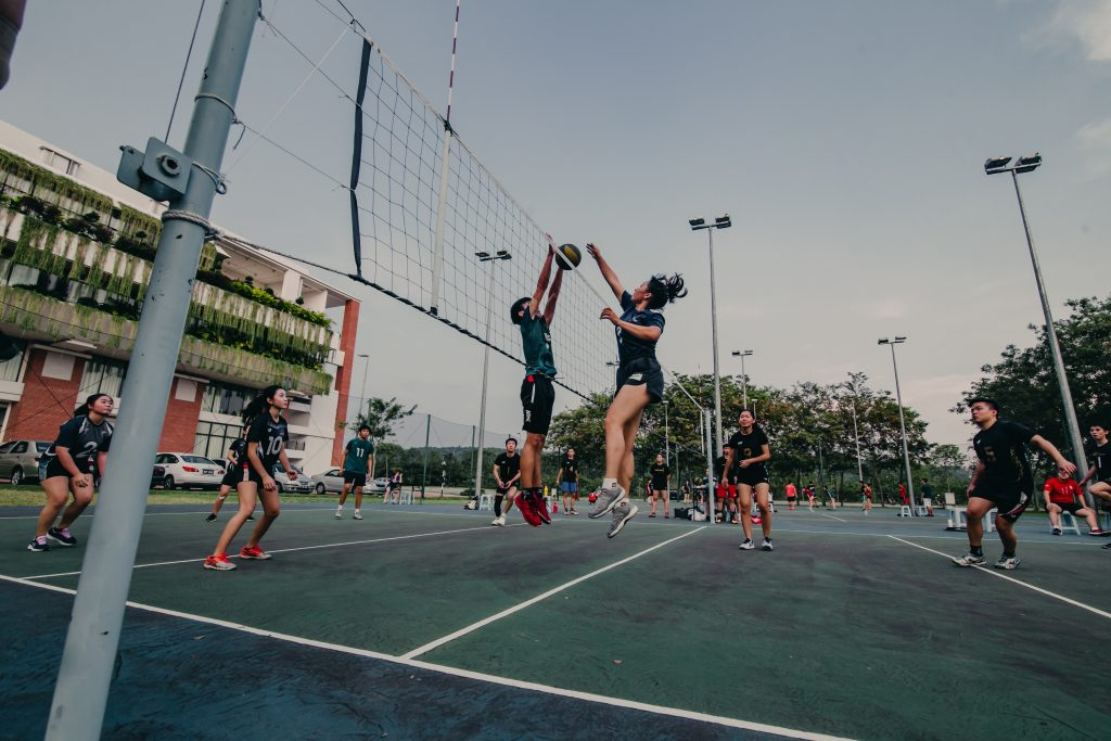People in sports attire playing volleyball in a field