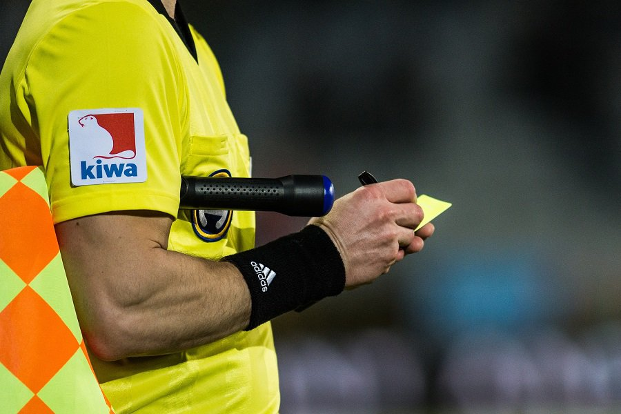 Soccer referee carrying a flag and holding a yellow card