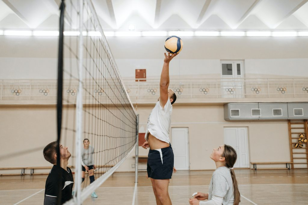 A volleyball reaching for the ball over the net