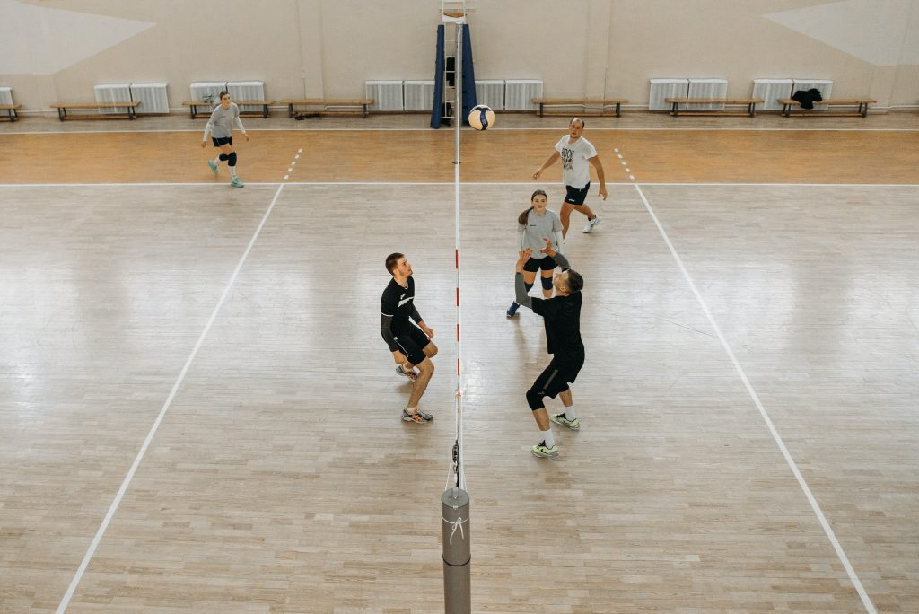 A bird's eye view of a volleyball court with players setting a play