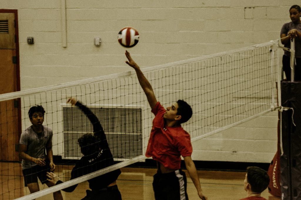 A volleyball player jumping for the ball to hit towards the opposite team