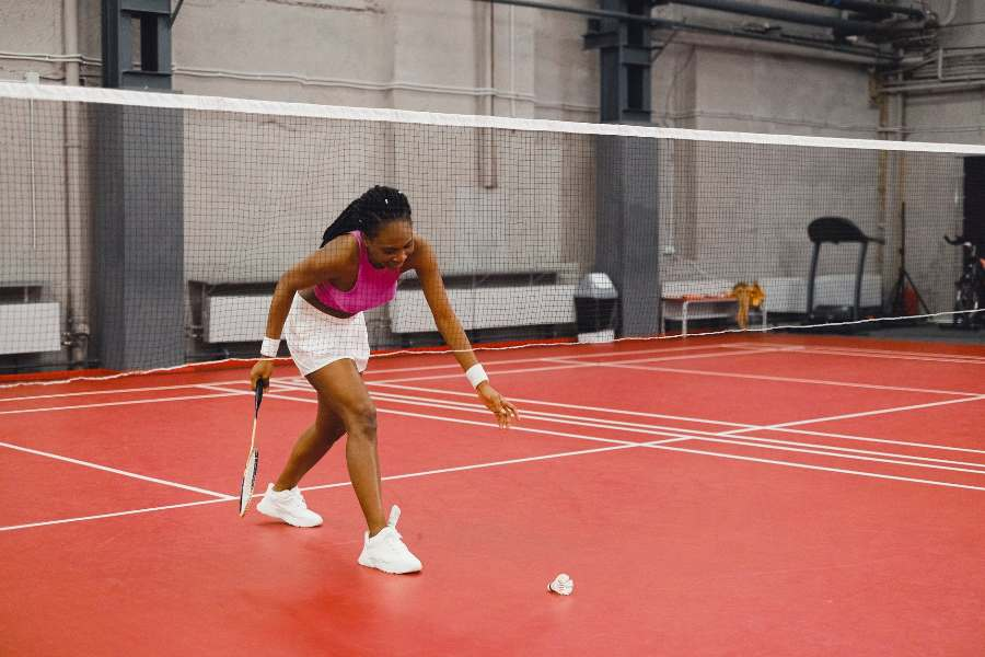 Woman picking up a shuttlecock while holding a racket