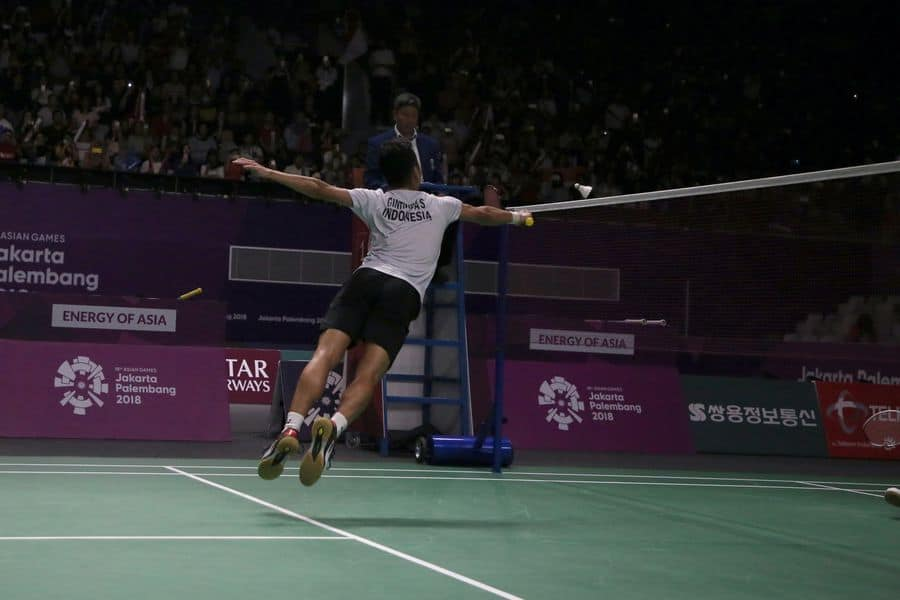 Man trying to hit back a shuttlecock in a badminton game