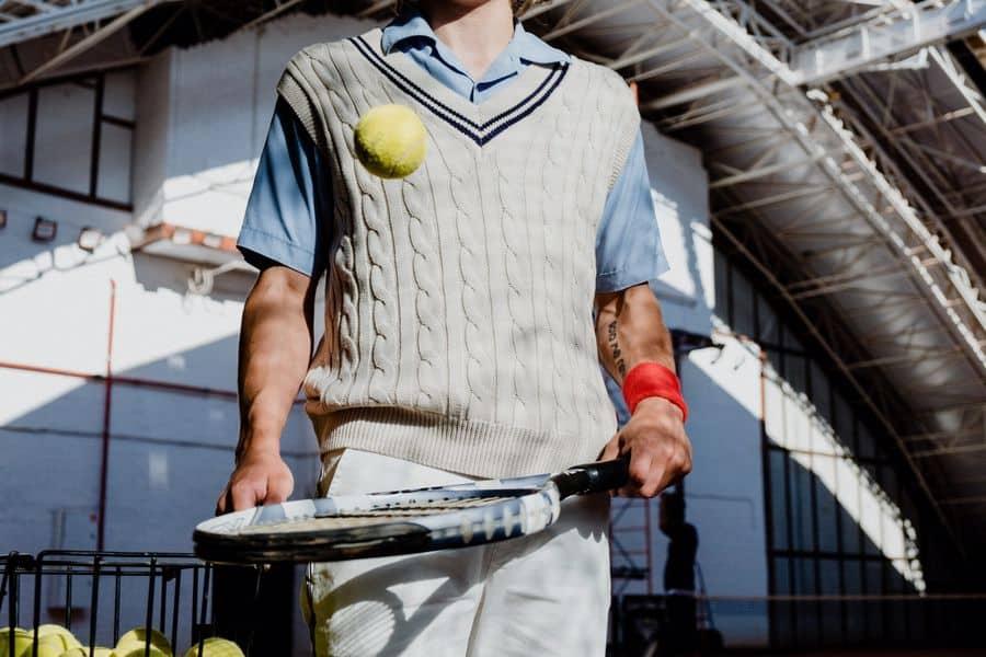 Man holding a tennis racquet and ball