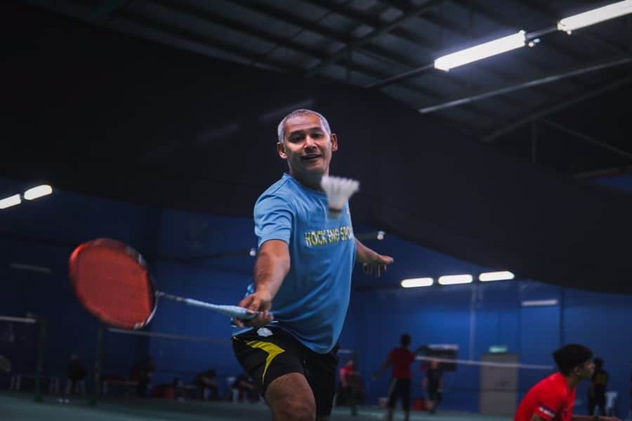 Man attempting to hit a shuttlecock with a racket